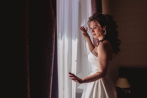 Mooie jonge bruid staat bij het raam in de hotelkamer te wachten. ochtend van de bruid op trouwdag. gelukkige bruid wacht om bruidegom te ontmoeten. auteursrechtruimte