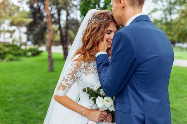 Mooie jonge bruidspaar in de natuur, verliefde paar