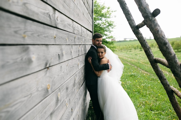 Mooie jonge bruidspaar staat in de buurt van het oude houten huis