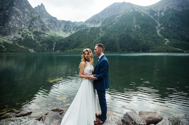 Mooie jonge bruidspaar van bruid en bruidegom permanent op de groene helling, heuvel. zonsondergang in de karpaten