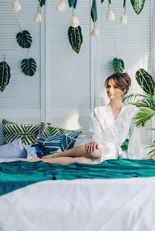 Mooie jonge bruidzitting op een bed dat met een groene deken in een ruimte met bloemen wordt behandeld