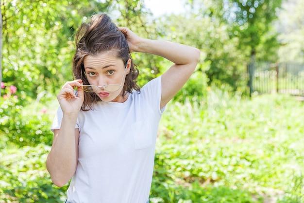 Mooie jonge brunete vrouw met bruin haar in trendy gele zonnebril rusten en glimlachend op park of tuin