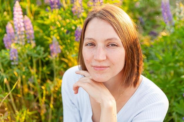 Mooie jonge brunete vrouw rusten op zomer veld met bloeiende wilde bloemen