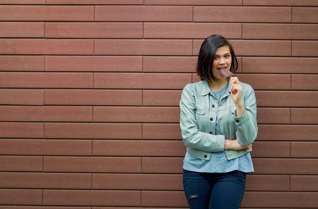 Mooie jonge brunette blanke vrouw in een grijs leren jasje proeft ijs in chocolade glazuur in de buurt van een getextureerde bruine bakstenen muur.