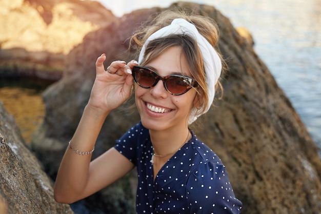 Mooie jonge brunette dame in trendy zonnebril en witte hoofdband poseren buiten op zonnige dag, glimlachend vreugdevol zittend op grote steen