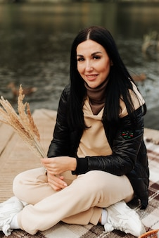 Mooie jonge brunette gekleed in de herfst houdt korenaren in haar handen