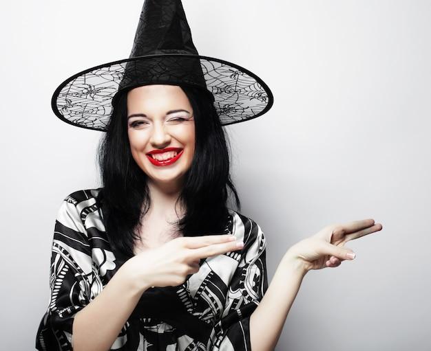Mooie jonge brunette heks met zwarte hoed, geïsoleerd tegen een witte achtergrond