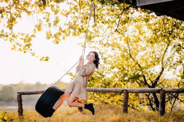 Mooie jonge brunette meisje in beige jurk rijdt een band aan een touw aan een boom.