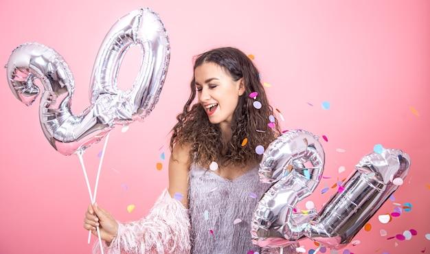 Mooie jonge brunette meisje met krullend haar poseren op een roze studio achtergrond met confetti en zilveren ballonnen voor het nieuwe jaar concept in haar hand te houden