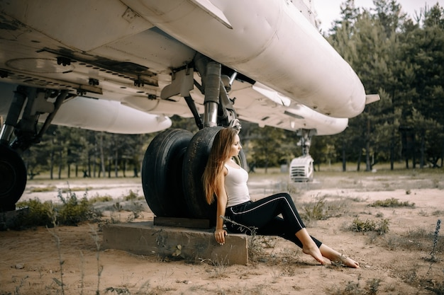 Mooie jonge brunette meisje staat op de ruimte van oude militaire vliegtuigen