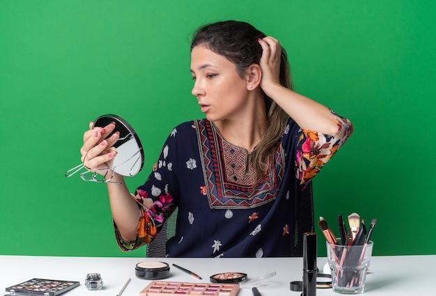 Mooie jonge brunette meisje zit aan tafel met make-up tools hand op haar haar te zetten en spiegel te kijken