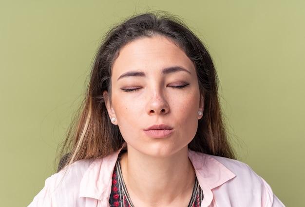 Mooie jonge brunette meisje zit met gesloten ogen geïsoleerd op olijfgroene muur met kopieerruimte