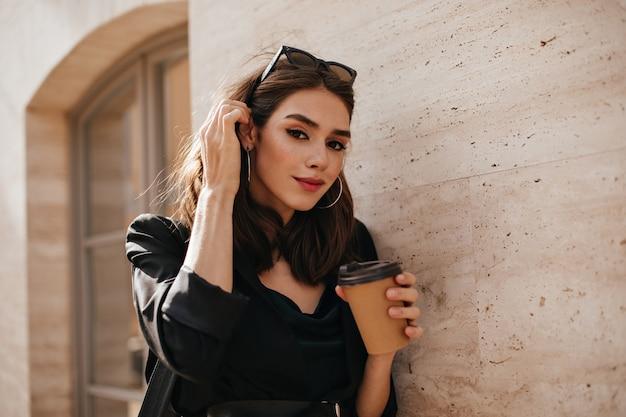 Mooie jonge brunette met trendy make-up, bril op hoofd, donkere jurk en jas die in de buurt van een beige muur in daglichtstad staat en een kopje koffie vasthoudt