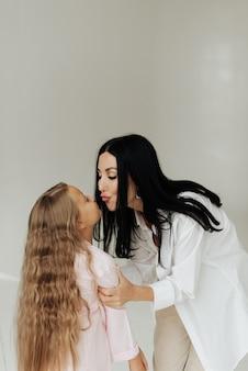 Mooie jonge brunette moeder kuste haar dochter met lang blond haar op een witte achtergrond