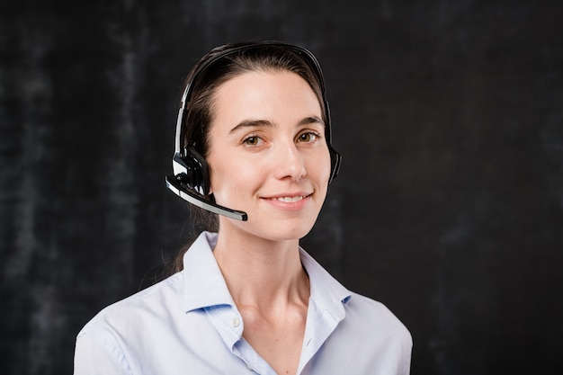 Mooie jonge brunette operator met hoofdtelefoon praten met klanten tijdens het werk voor camera tegen zwarte achtergrond