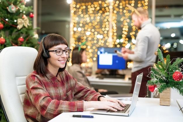 Mooie jonge brunette operator met hoofdtelefoon typen voor laptop tijdens het organiseren van werk op kantoor op kerstdag
