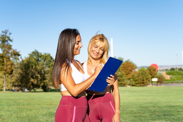 Mooie jonge brunette vrouw, een instructeur en persoonlijke sport- en fitness trainer, traint een aantrekkelijke oudere vrouw buitenshuis en vertelt haar hoe ze oefeningen moet doen door het in haar notitieblok uit te leggen