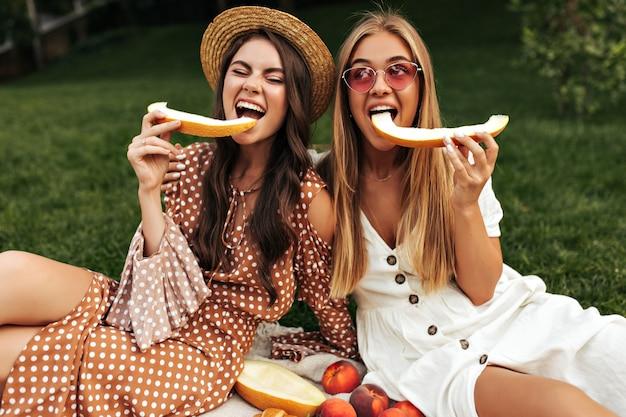 Mooie jonge brunette vrouw en aantrekkelijk gebruind blond meisje in stijlvolle zomerjurken eten meloen en picknicken buiten