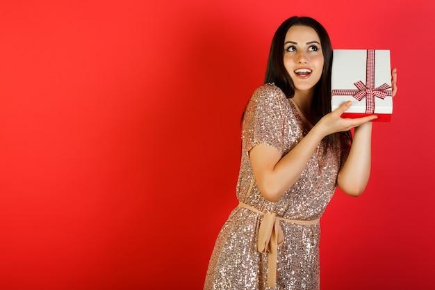 Mooie jonge brunette vrouw gekleed in beige jurk schudt geschenkdoos om erachter te komen wat erin zit.