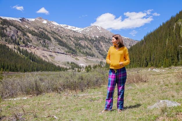 Mooie jonge brunette vrouw geniet van prachtige berglandschap tijdens het reizen.