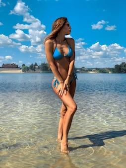 Mooie jonge brunette vrouw in blauwe zwembroek poseren op het strand in warme zomerdag