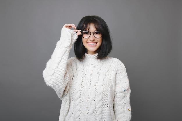 Mooie jonge brunette vrouw in witte trui bril dragen en glimlachen naar de camera op grijs