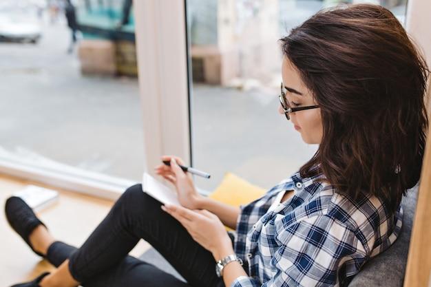 Mooie jonge brunette vrouw in zwarte bril zittend op venster thuis, schrijven in notitieblok. comfortabele werkplek, analyseren, opgewekte stemming, slimme student.
