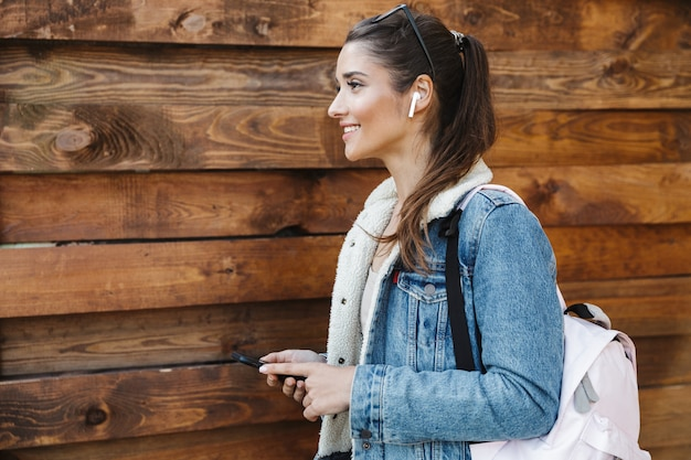 Mooie jonge brunette vrouw jas dragen, dragen rugzak buiten lopen over houten muur, luisteren naar muziek met koptelefoon, mobiele telefoon te houden