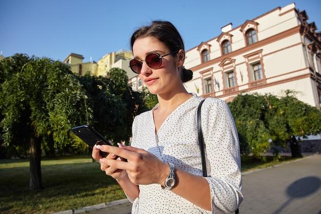 Mooie jonge brunette vrouw met broodje kapsel zonnebril dragen tijdens het lopen door de straat op warme zonnige dag, smartphone in opgeheven handen houden en op het scherm kijken