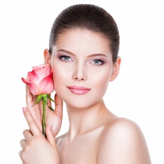 Mooie jonge brunette vrouw met een gezonde huid en roze bloemen in de buurt van gezicht - geïsoleerd op wit.