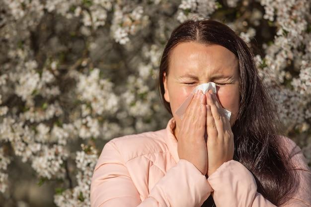 Mooie jonge brunette vrouw met een sterke allergische reactie tijdens de lente, niezen, benauwdheid, gezondheidszorgconcept