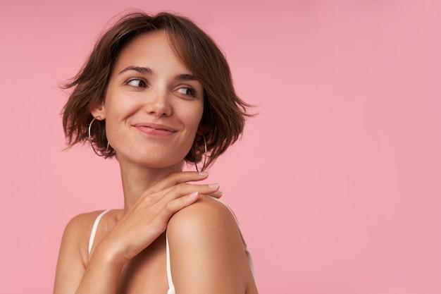 Mooie jonge brunette vrouw met kort kapsel kijkt over haar schouder en lacht vrolijk, draagt witte top terwijl poseren, hand op haar nek houdt