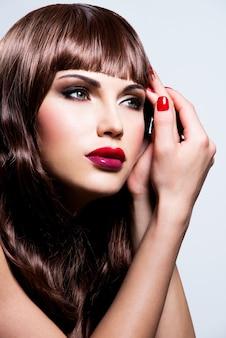 Mooie jonge brunette vrouw met lang krullend haar poseren close-up portret van een vrouwelijk model met fashion make-up.