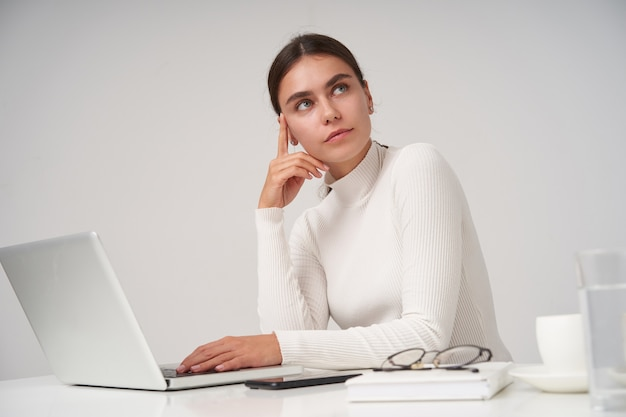 Mooie jonge brunette vrouw met paardenstaart kapsel werkt met haar laptop op kantoor, houdt haar hoofd met opgeheven hand en kijkt peinzend opzij, geïsoleerd over witte muur