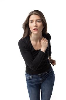 Mooie jonge brunette vrouw opschieten. geïsoleerde afbeelding op de witte muur.