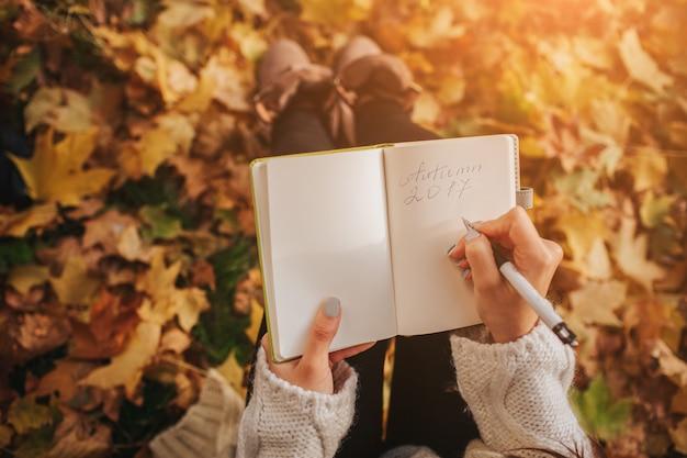 Mooie jonge brunette zittend op gevallen herfstbladeren in een park