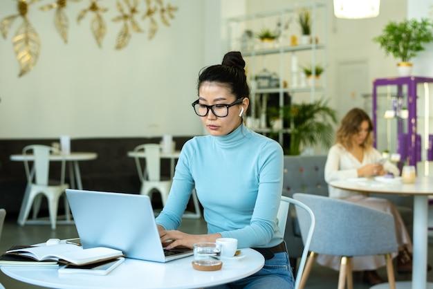 Mooie jonge casual vrouw met draadloze koptelefoon typen voor laptop terwijl netwerken door tafel in café