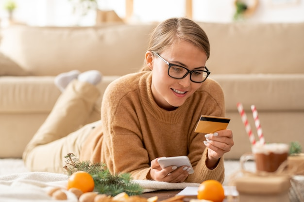 Mooie jonge casual vrouw met smartphone en creditcard kijken naar persoonlijke gegevens terwijl ze gaat betalen voor online bestelling
