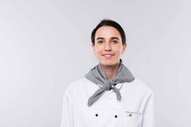 Mooie jonge chef-kok in wit uniform die je met een glimlach bekijkt terwijl hij geïsoleerd voor de camera staat
