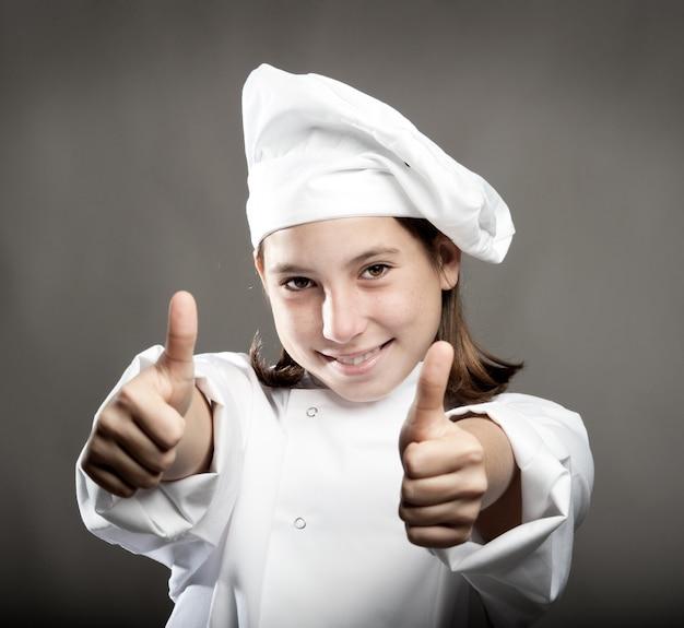 Mooie jonge chef-kok met duimen omhoog