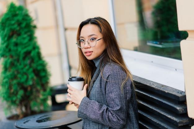 Mooie jonge chinese student met een kopje koffie in de straat