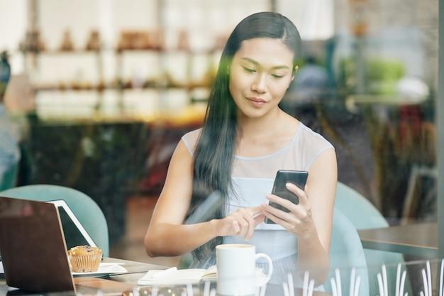 Mooie jonge chinese vrouw die aan tafel in het café werkt en tekstberichten in smartphone controleert