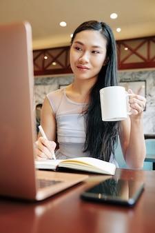 Mooie jonge chinese vrouw mok koffie drinken tijdens het werken op laptop in plaatselijk café na lessen op de universiteit