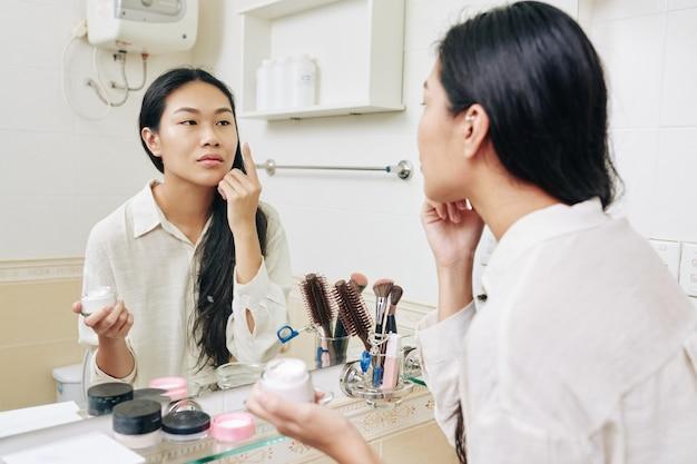 Mooie jonge chinese vrouw plumping en hydraterende moisturizer voor spiegel in de badkamer toe te passen