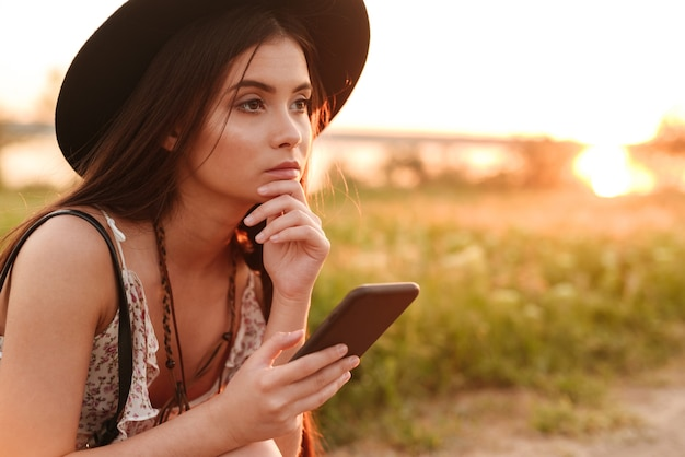 Mooie jonge dame buiten in het veld met behulp van mobiele telefoon met hoed.