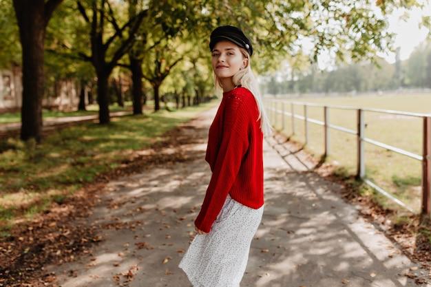 Mooie jonge dame casual trendy kleding dragen in de herfst park. mooie blonde ziet er schattig uit op het platteland.