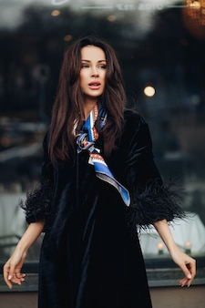 Mooie jonge dame die een modieuze zwarte jas draagt terwijl ze koffie houdt en in de buurt van de auto staat. mode stad concept