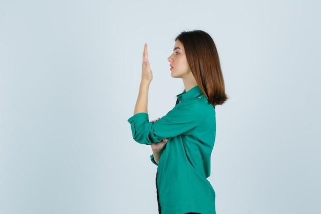 Mooie jonge dame die haar opgeheven handpalm in groen overhemd bekijkt en peinzend kijkt. .