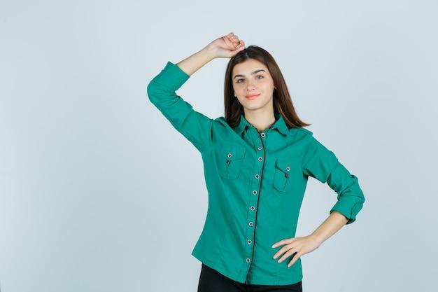 Mooie jonge dame die hand op hoofd in groen overhemd houdt en zelfverzekerd kijkt, vooraanzicht.