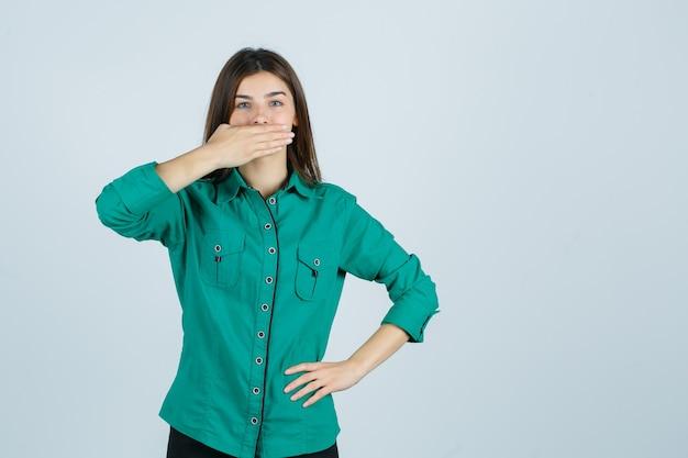 Mooie jonge dame die hand op mond in groen overhemd houdt en verbaasd kijkt. vooraanzicht.
